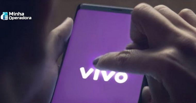 Pessoa utilizando o celular, enquanto na tela aparece a logomarca da Vivo na cor branca com o fundo roxo.