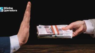 Imagem de uma pessoa oferecendo dinheiro para outra que parece recusar.