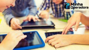 Quatros crianças utilizando tabletes.