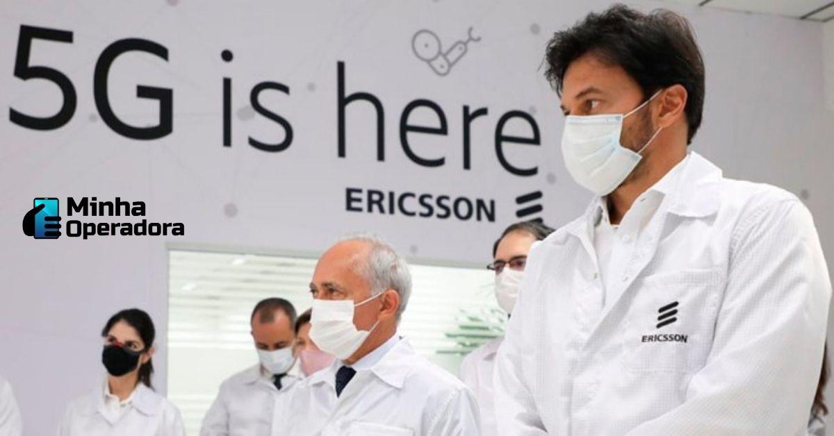 """O ministro das Comunicações aparece em primeiro plano, ao lado de funcionários da empresa. Na parede está escrito: """"5G is here""""."""