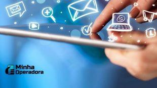 Usuário toca no celular que está rodeado de figuras que remetem a serviços de telecomunicações.