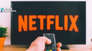 Mão aponta o controle para a TV com o símbolo da Netflix.