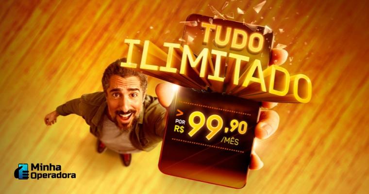 Marcos Mion levanta um celular que traz a oferta na tela.