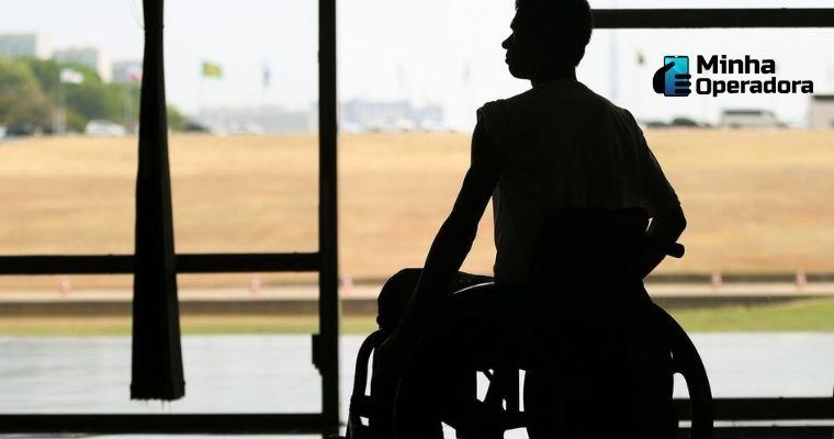 Imagem de uma homem contra-luz em uma cadeira de rodas.