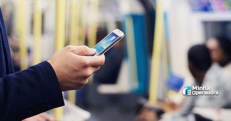 Pessoa utilizando o celular no transporte público