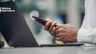 Pessoa utilizando o smartphone com o notebook aberto.