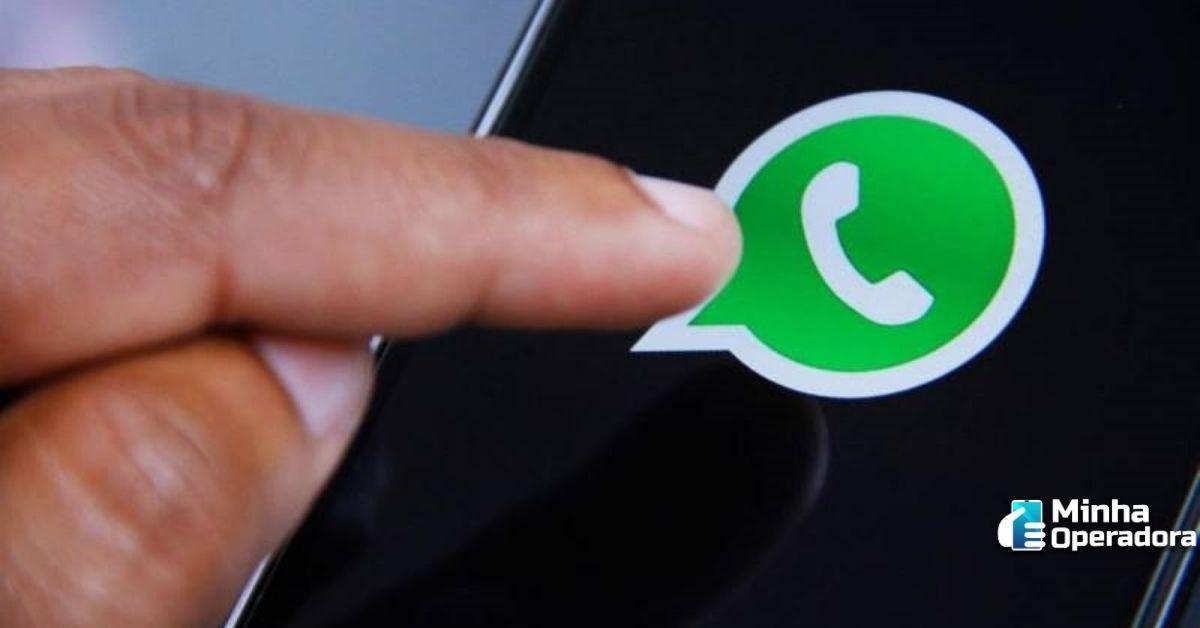 A mão de um usuário tecla o símbolo do WhatsApp na tela do celular.