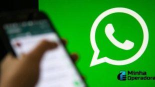 Em primeiro plano aparece um celular desfocado, com a logomarca do WhatsApp ao fundo.
