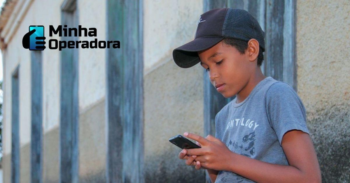 Menino de boné utilizando o celular na frente de casa.