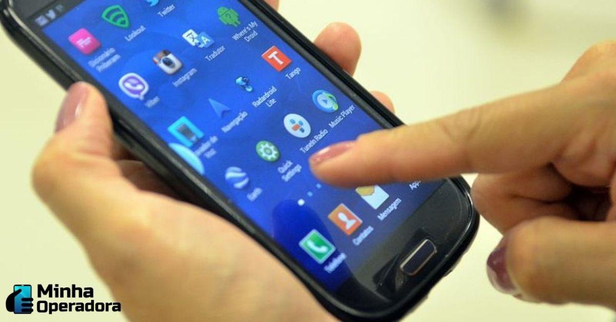 Mão de uma pessoa teclando um smartphone.
