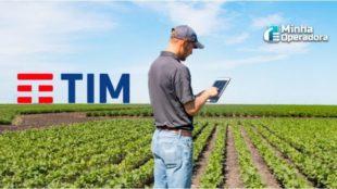 Homem utilizando o tablet no meio da plantação, com o logotipo da TIM no horizonte.