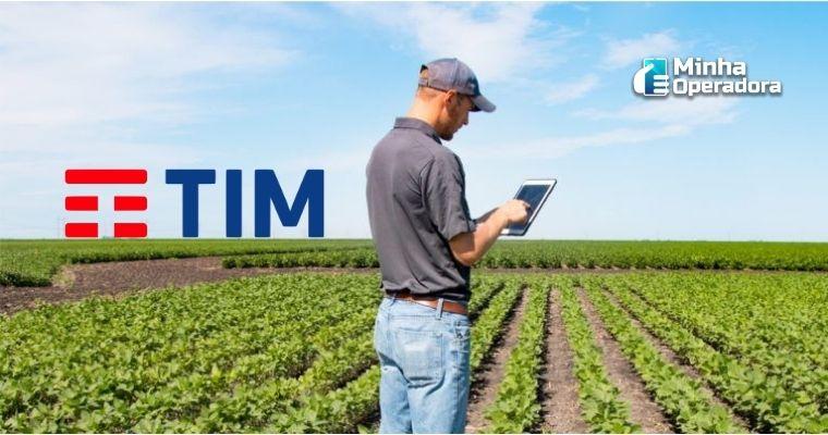 Homem utilizando o tablet no meio da plantação com o logotipo da TIM no horizonte.