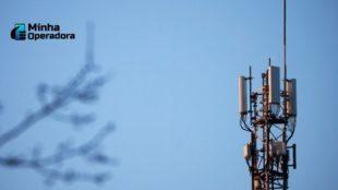 Fotografia com uma antena de celular e um galho de árvore desfocado na frente.
