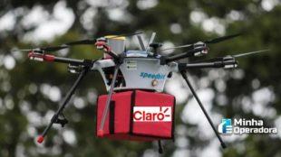 Drone carregando um pacote com o logotipo da Claro