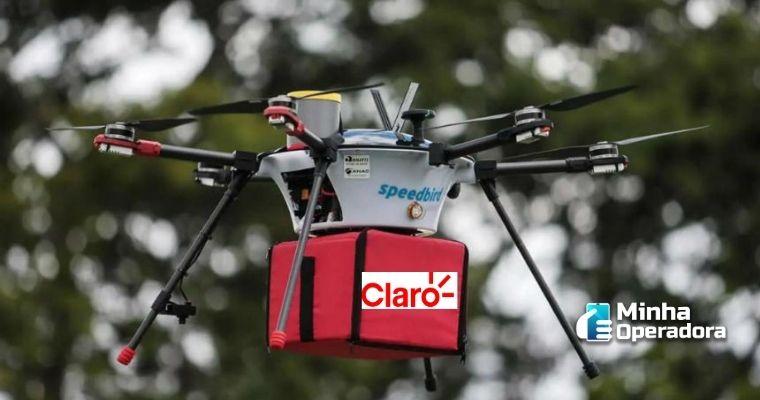 Drone carregando pacote com o logotipo da Claro.