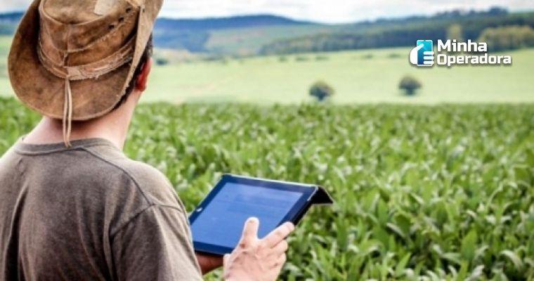 Imagem de um homem de chapéu utilizando o tablete enquanto olha a plantação.