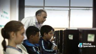 Alunos utilizando o computador com orientação do professor.