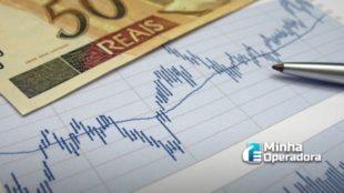 Imagem de um balanço financeiro e uma nota de R$ 50 e uma caneta sobre o documento.
