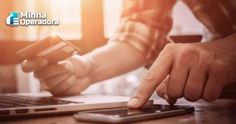 Pessoa segurando o cartão em uma mão e apontando para o celular com a outra.