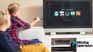 Duas crianças assistindo a Netflix na TV.