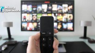 Controle apontado para uma TV com um catálogo de canais na tela.