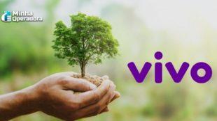 Mão segurando uma pequena árvore e o logotipo da Vivo ao lado