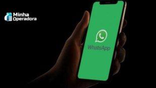 Mão segurando um celular com o aplicativo do WhatsApp aberto.