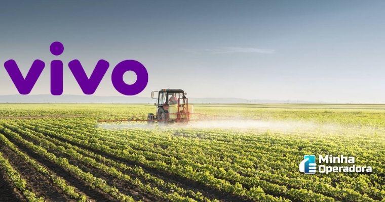 Colheitadeira passando por uma plantação, com o logotipo da Vivo no horizonte.